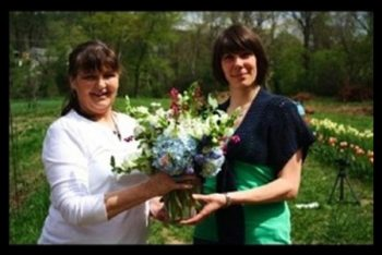 Enchanted Florist hands off a centerpiece to the Hindsight Bride