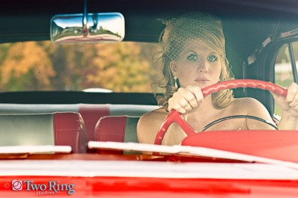 Bride in a birdcage veil drives a cherry red vintage car