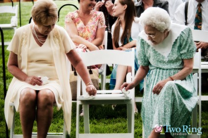 Two grandmothers look at a wedding ceremony program