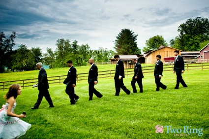 Groomsmen in a line while a flower girl runs in the opposite direction
