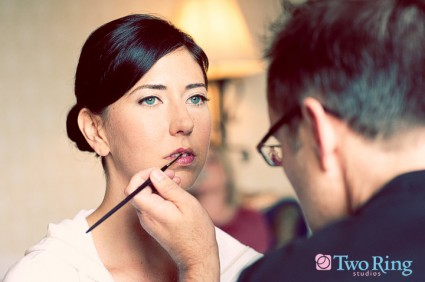 Bride with blue eyes getting bright pink lipstick applied