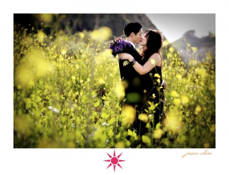 Newly weds dresses in black for an anniversary shoot kiss in a field while the bride holds a purple bouquet of flowers