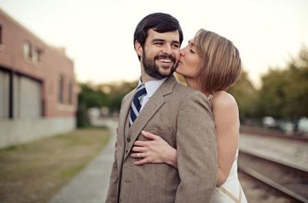 short haired bride kisses groom outside