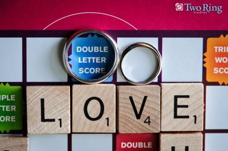 Wedding rings on a scrabble board spelling LOVE