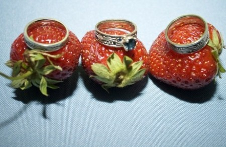Three wedding rings on three whole strawberries