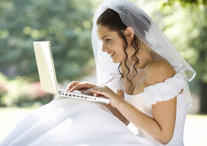 Bride in wedding gown types on computer