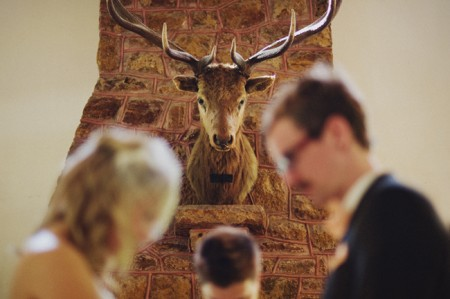 bride and groom exchange vows under the watchful eye of a deer head trophy