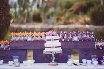 purple and red wedding cake with candy apples