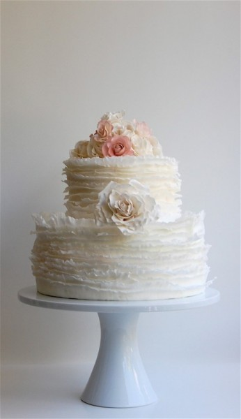 two tier cake with delicate ruffles and a gum paste rose on top
