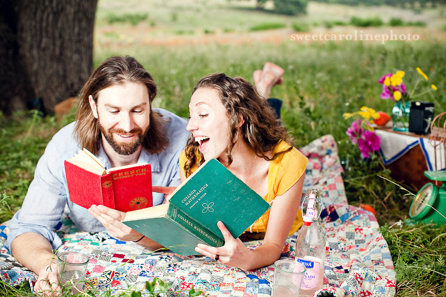 Engaged couple read vintage books on an antique quilt