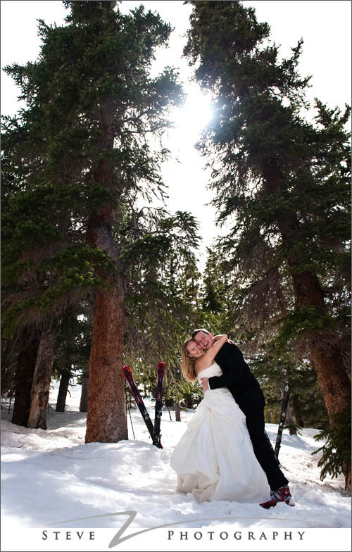 Bride and groom hug under pine tree with skis in the background