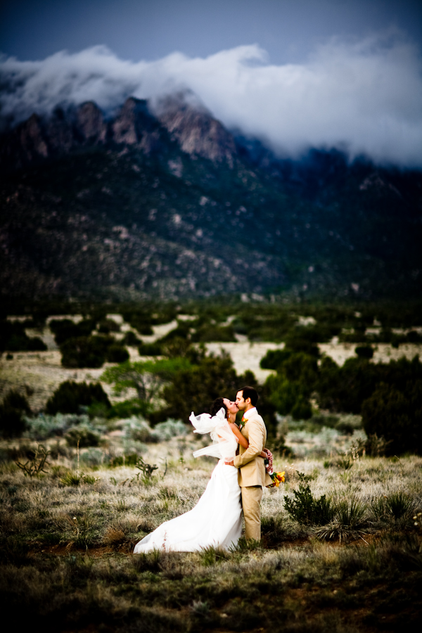 bride and groom kiss in front of a mountain range