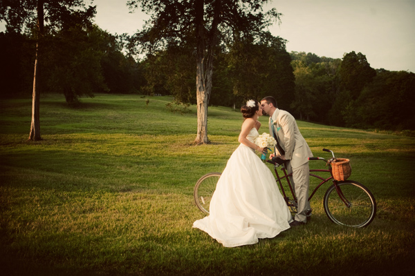 bride and groom on a bicycle kissing