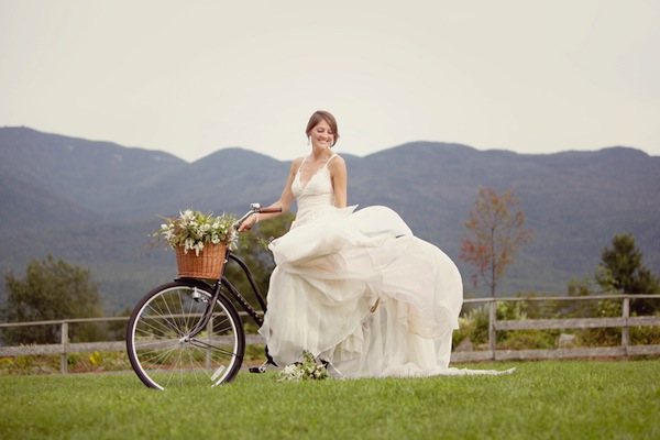bride on bicycle in front of New Hampshire Mountains