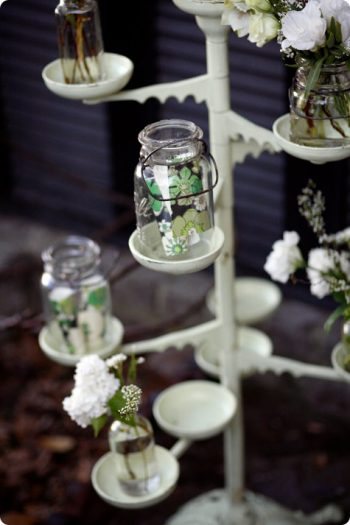 painted mason jars in a plant stand