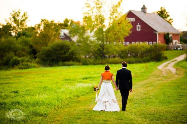 Bride in Orange Bolero walks to a red barn with Groom