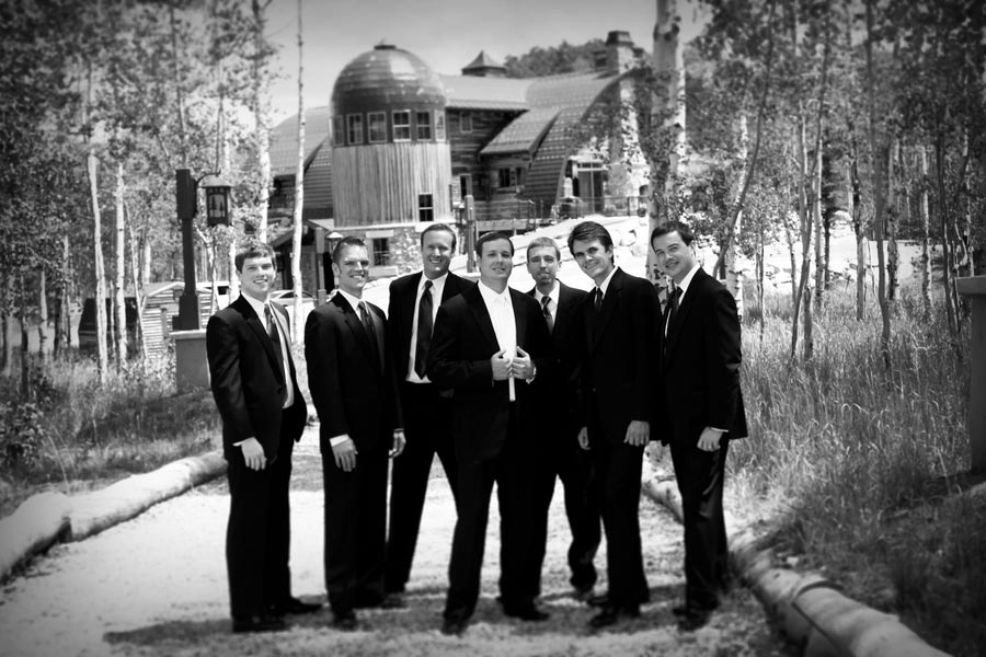 groom and groomsmen in front of a barn