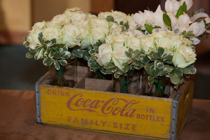 white roses in a vintage yellow and red coca-cola box