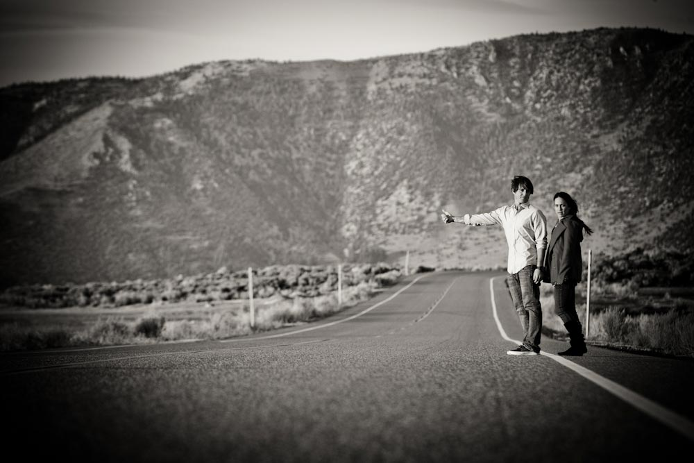 man and woman hitch hike in the desert