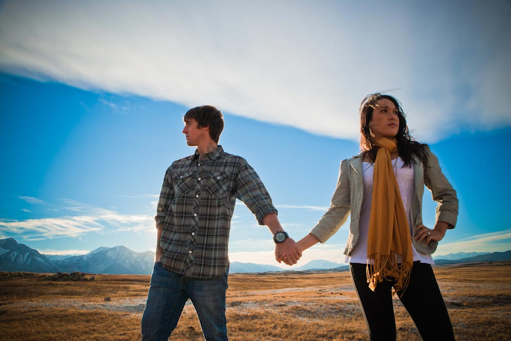 man and woman holding hands in the mounatin desert