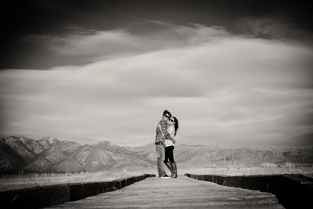 balck and white of engaged couple of on lake dock