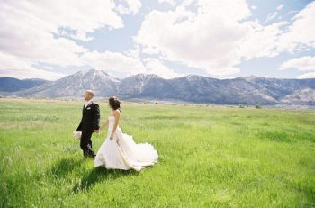 bride and groom walk across a meadow with mountains in the backgrond