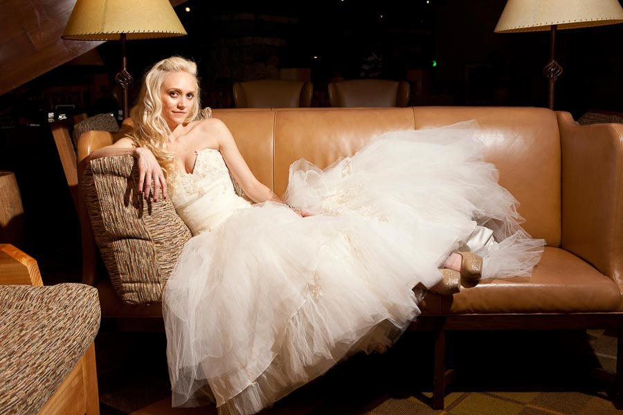 Beautiful bride lounges on a leather sofa