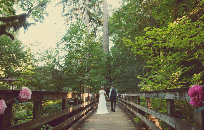Camp wedding bride and groom cross a rustic wooden bridge
