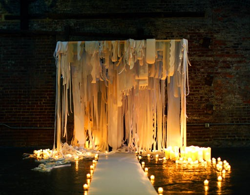 wedding ceremony site lit with candles and draped with fabric streamers