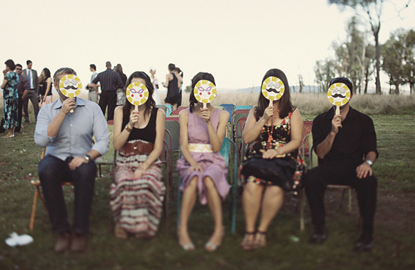 wedding guests don masks for the photo booth