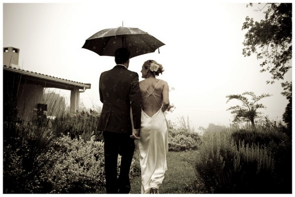 Black and white picture of a bride and groom in the rain
