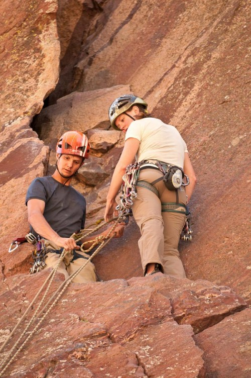 engaged rock climbing couple at the top of a pitch