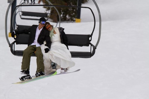 bride and groom ride a ski lift on Mammoth Mountain