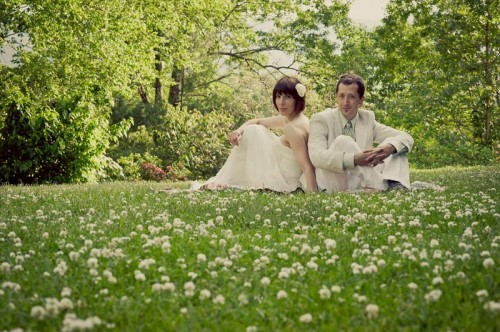 Hindsight Bride and Groom sit in afield of flowers