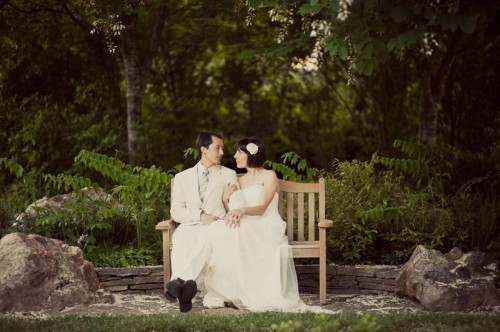 Hindsight Bride and groom sit on a garden bench