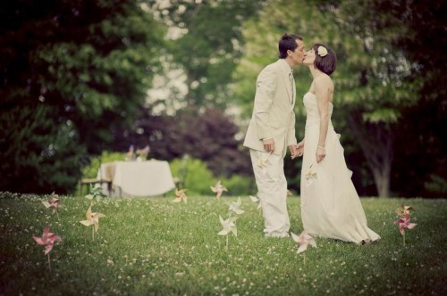Hindsight Bride and groom kiss in a field of DIY pinwheels