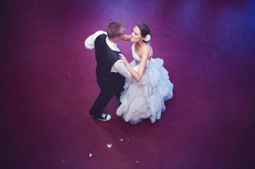 bride and groom dance on a purple dance floor