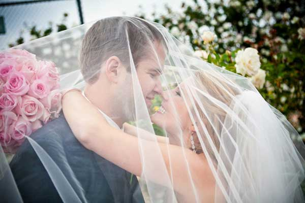Bride and groom under brides veil