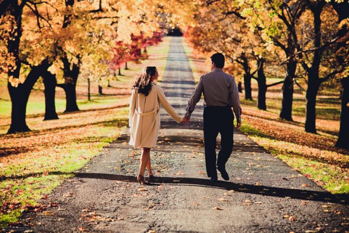 Couple walks down a tree-lined country road in autumn