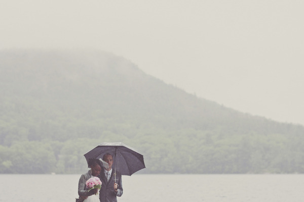 brides and groom nuzzle under an umbrella on a rainy day by the lake