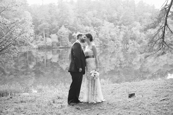 black and white bride and groom by a lake