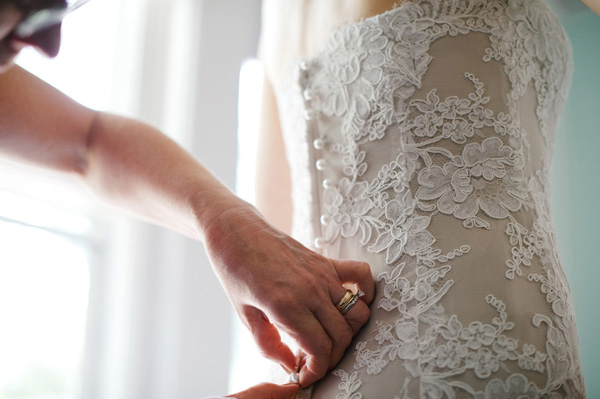 bride buttoning her lace gown