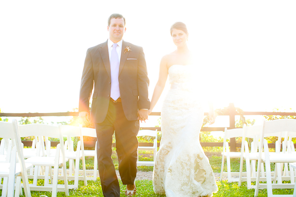 Bride and groom holding hands in a sun flare