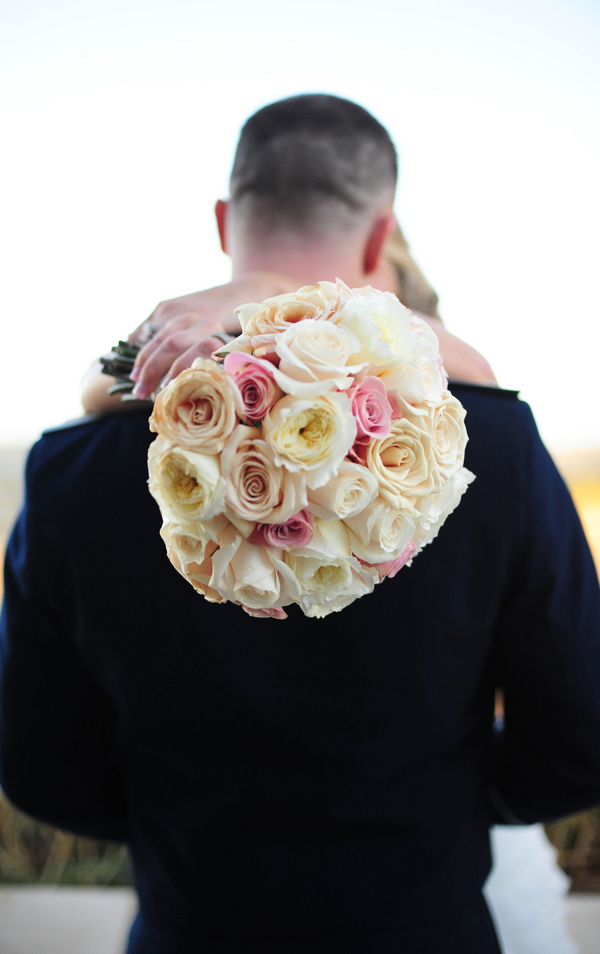 bride holding pink and white rose bouquet kisses her groom
