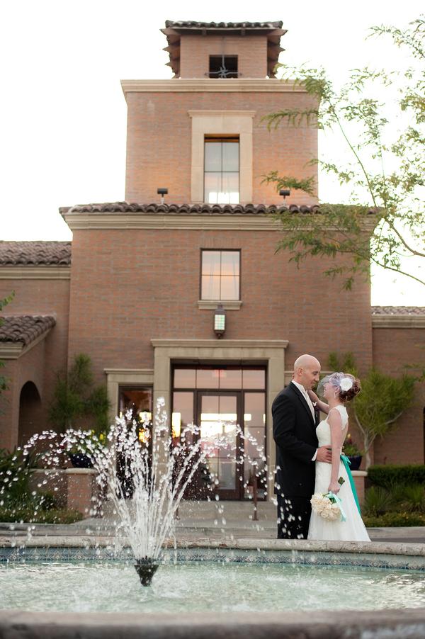bride and groom embrace near a fountain