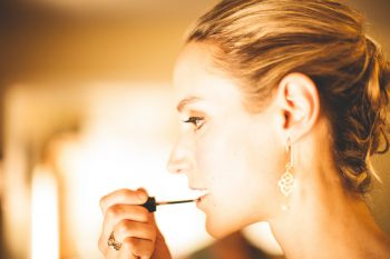 mountain ranch bride putting on lip gloss