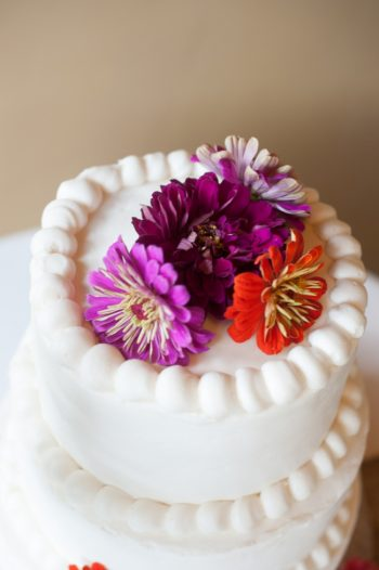 rustic wedding cake with fresh red and purple flowers