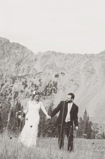 bride and groom in a meadow near arapahoe basin