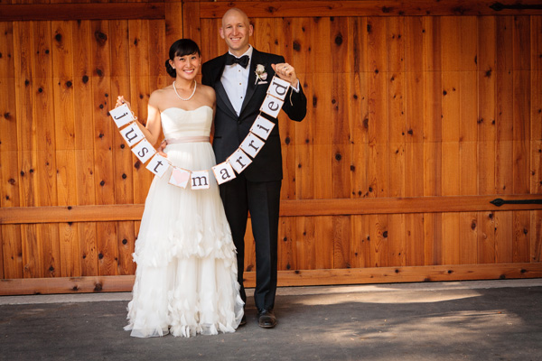 bride and groom hold a just married sign