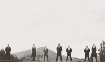 black and white groomsmen in front of mountain